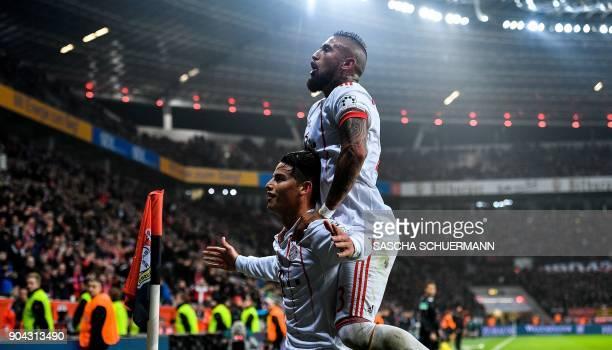 Bayern Munich's midfielder James Rodriguez celebrates after scoring with Bayern Munich's Chilean midfielder Arturo Vidal during the German First...