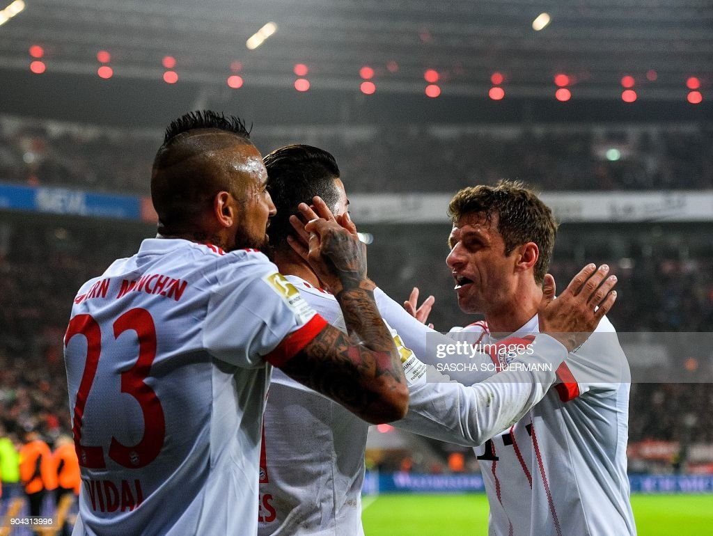 Bayern Munich's midfielder James Rodriguez (C) celebrates after scoring with his teammates during the German First division Bundesliga football match Bayer Leverkusen vs FC Bayern Munich on January 12, 2018 in Leverkusen, western Germany. /