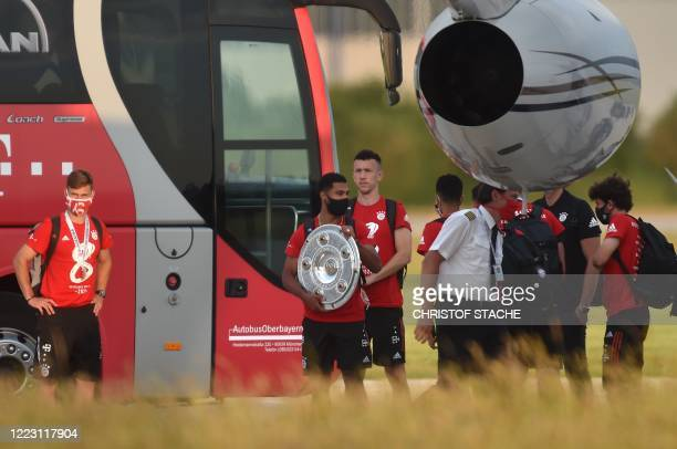 Bayern Munich's midfielder Serge Gnabry holds the trophy next to several players upon the team's arrival to the small airport in Oberpfaffenhofen...