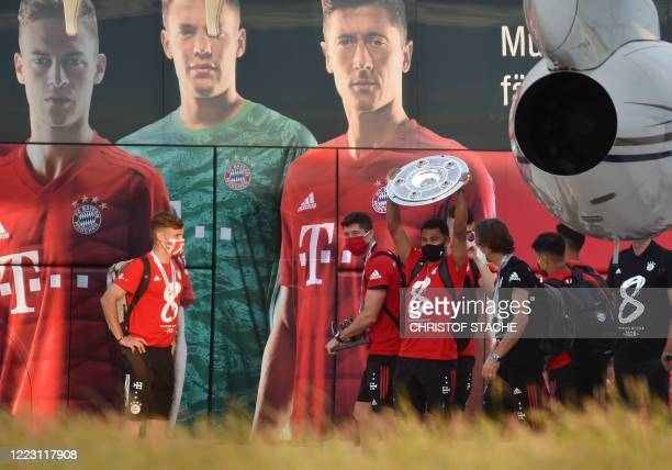 Bayern Munich's midfielder Serge Gnabry holds the trophy next to several team players upon the team's arrival to the small airport in...