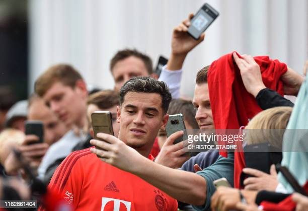 Bayern Munich's new Brazilian midfielder Philippe Coutinho poses for pictures with fans after a training session at the team's training ground in...