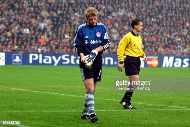 Bayern Munich's Oliver Kahn takes his gloves off as he leaves the pitch after being substituted with an injury