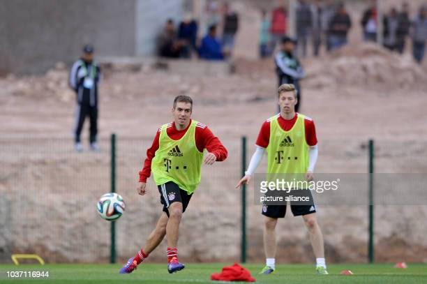 FCBayern Munich's Philipp Lahm and Mitchell Weiser take part in a training session at the stadium'Stade Adrar' in Agadir Morocco 20December 2013...