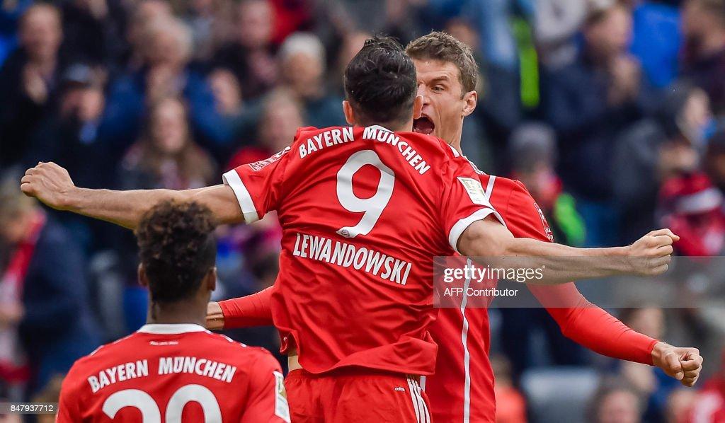 Bayern Munich's players celebrate after Polish striker Robert Lewandowski scored the 3-0 during the German First division Bundesliga football match FC Bayern Munich v Mainz 05 in Munich, southern Germany, on September 16, 2017. / AFP PHOTO / Guenter SCHIFFMANN / ALTERNATIVE