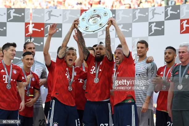 Bayern Munich's players lift the trophy during the celebration for the 28th German football championship after the German first division Bundesliga...