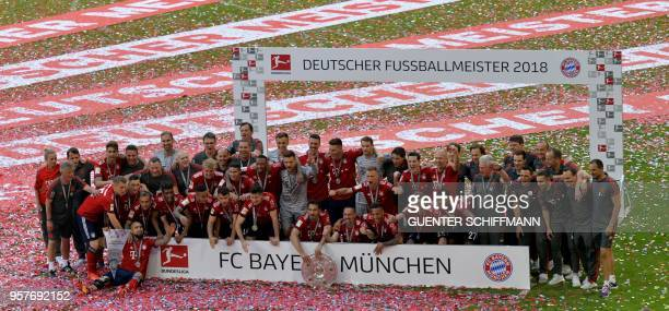 TOPSHOT Bayern Munich's players pose with their trophy after their victory at the end of the German first division Bundesliga football match FC...