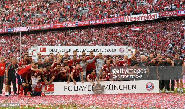 Bayern Munich's players pose with their trophy after their victory at the end of the German first division Bundesliga football match FC Bayern Munich...