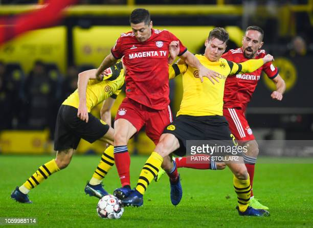 Bayern Munich's Polish forward Robert Lewandowski and Dortmund's Polish defender Lukasz Piszczek vie for the ball during the German first division...