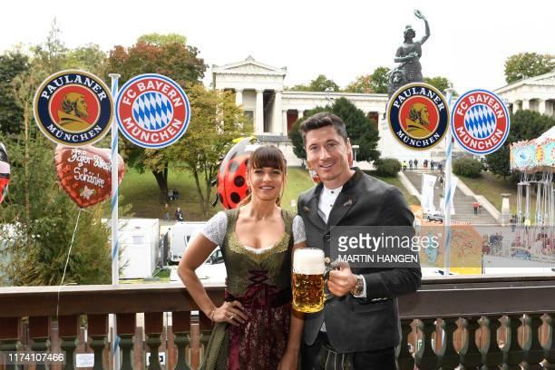 Bayern Munich's Polish forward Robert Lewandowski and his wife Anna Lewandowska pose during the football club's annual visit at the Oktoberfest beer...