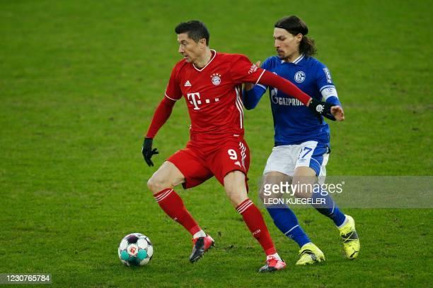 Bayern Munich's Polish forward Robert Lewandowski and Schalke's French midfielder Benjamin Stambouli vie for the ball during the German first...