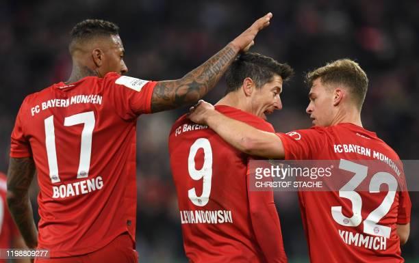 Bayern Munich's Polish forward Robert Lewandowski celebrates scoring with his team-mates German midfielder Joshua Kimmich and German defender Jerome...