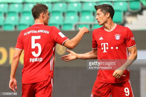 Bayern Munich's Polish forward Robert Lewandowski celebrates scoring the third goal for his team with Bayern Munich's French defender Benjamin Pavard...