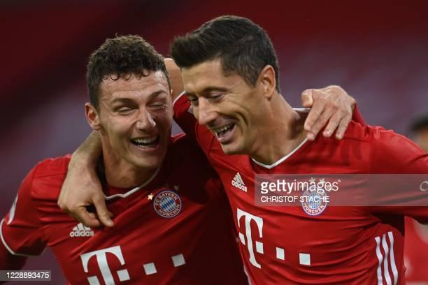 Bayern Munich's Polish forward Robert Lewandowski celebrates scoring his third side's goal with Bayern Munich's French defender Benjamin Pavard...