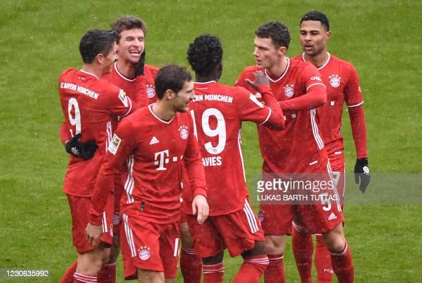 Bayern Munich's Polish forward Robert Lewandowski celebrates scoring the opening goal with teammates during the German first division Bundesliga...