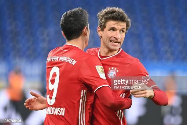 Bayern Munich's Polish forward Robert Lewandowski celebrates scoring the 0-2 goal with his team-mate Bayern Munich's German forward Thomas Mueller...