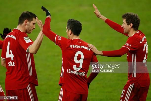 Bayern Munich's Polish forward Robert Lewandowski celebrates scoring the 0-2 goal with his team-mates during the German first division Bundesliga...