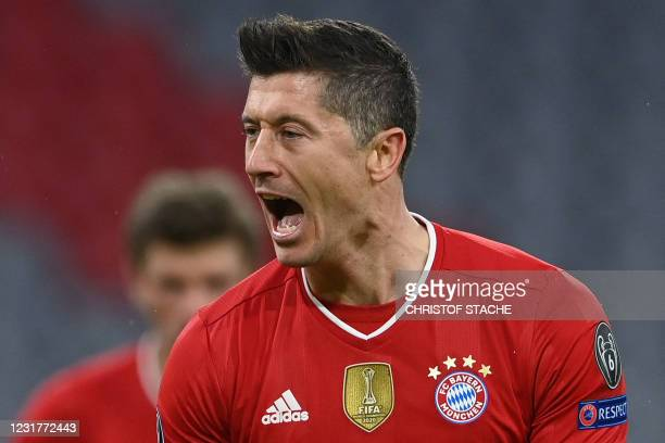 Bayern Munich's Polish forward Robert Lewandowski celebrates scoring the opening goal from the penalty spot during the UEFA Champions League Last-16,...