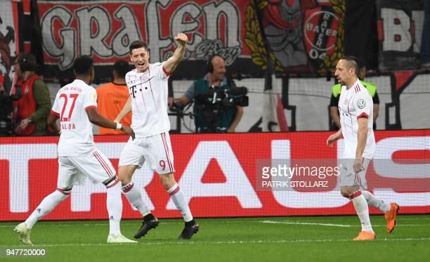 Bayern Munich's Polish forward Robert Lewandowski celebrates scoring with Bayern Munich's Austrian defender David Alaba and Bayern Munich's French...