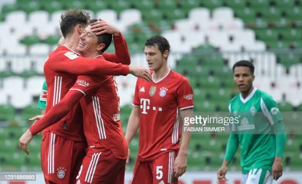 Bayern Munich's Polish forward Robert Lewandowski celebrates with Bayern Munich's German midfielder Leon Goretzka after scoring the 0-3 during the...