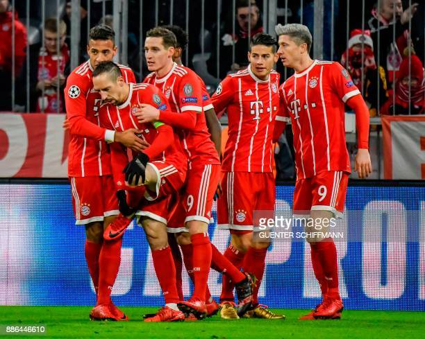 Bayern Munich's Polish forward Robert Lewandowski celebrates with teammates after scoring the opening goal during the UEFA Champions League football...