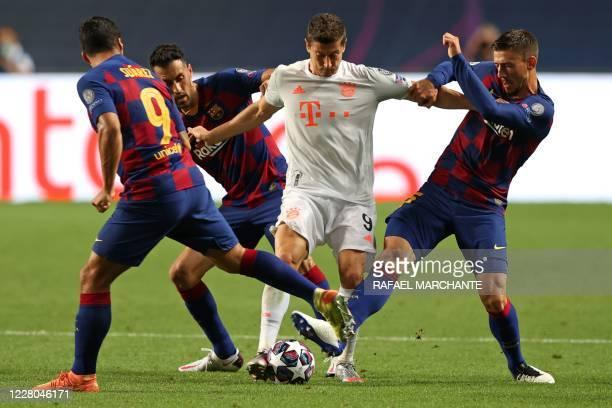 Bayern Munich's Polish forward Robert Lewandowski challenges Barcelona's Uruguayan forward Luis Suarez, Barcelona's Spanish midfielder Sergio...