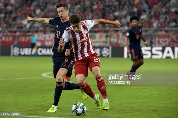 Bayern Munich's Polish forward Robert Lewandowski fights for the ball with Olympiakos' Greek defender Konstantinos Tsimikas during the UEFA Champions...