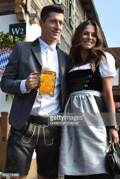 Bayern Munich's Polish forward Robert Lewandowski holds a beer mug as he poses with his wife Anna Stachurska during the traditional visit of members...
