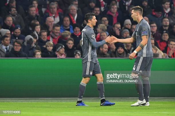 Bayern Munich's Polish forward Robert Lewandowski is congratulated by Bayern Munich's German defender Niklas Suele after scoring the opener during...
