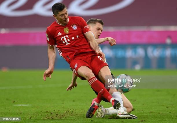 Bayern Munich's Polish forward Robert Lewandowski is is tackled by Moenchengladbach's German defender Matthias Ginter vie for the ball during the...