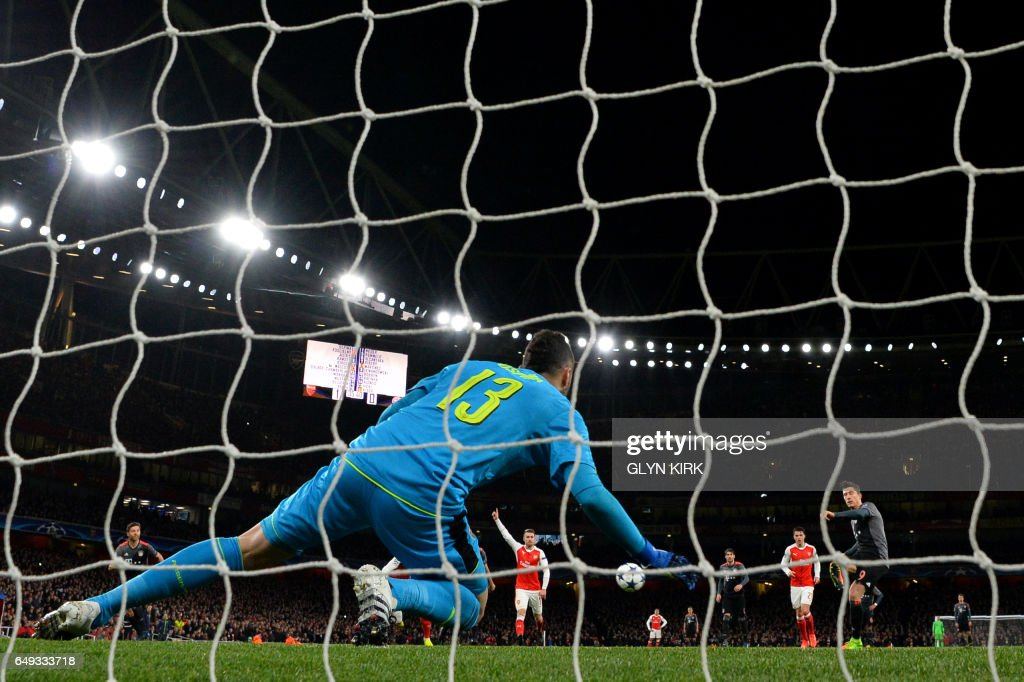 Bayern Munich's Polish forward Robert Lewandowski (R) scores a penalty past Arsenal's Colombian goalkeeper David Ospina during the UEFA Champions League last 16 second leg football match between Arsenal and Bayern Munich at The Emirates Stadium in London on March 7, 2017. /