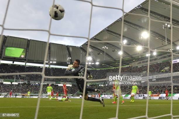 Bayern Munich's Polish forward Robert Lewandowski scores the 20 as Wolfsburg's Belgian goalkeeper Koen Casteels watches the ball during the German...