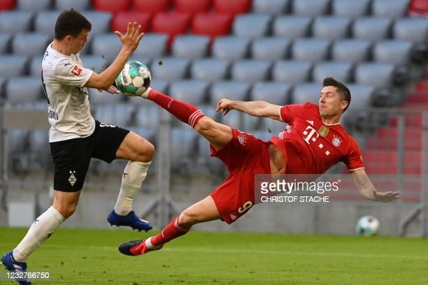 Bayern Munich's Polish forward Robert Lewandowski scores the 3-0 goal past Moenchengladbach's Austrian defender Stefan Lainer during the German first...