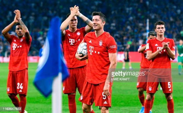Bayern Munich's Polish forward Robert Lewandowski takes the match ball for his hattrick as he and his teammates thank their fans after the German...