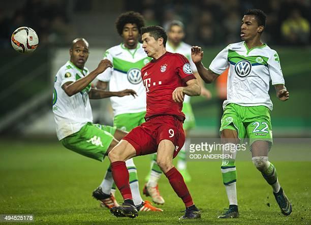 Bayern Munich's Polish forward Robert Lewandowski vie for the ball with Wolfsburg's Brazilian defender Naldo Wolfsburg's Brazilian defender Dante and...