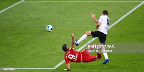 Bayern Munich's Polish forward Robert Lewandowski vies with Moenchengladbach's Austrian defender Stefan Lainer as he scores the 3-0 during the German...