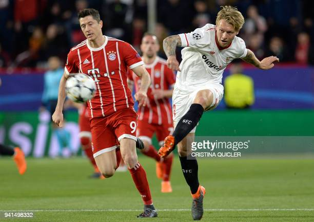Bayern Munich's Polish forward Robert Lewandowski vies with Sevilla's Danish defender Simon Kjaer during the UEFA Champions League quarterfinal first...