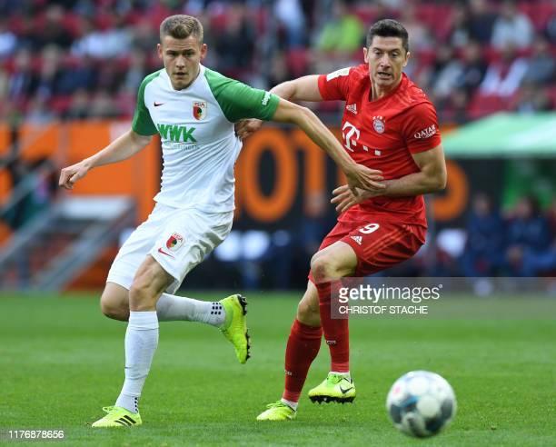 Bayern Munich's Polish striker Robert Lewandowski and Augsburg's Icelandic striker Alfred Finnbogason vie for the ball during the German first...