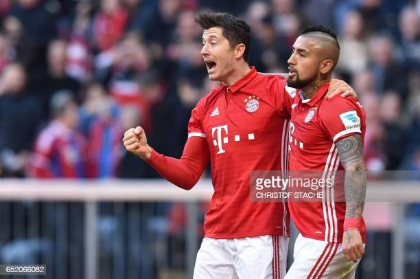 Bayern Munich's Polish striker Robert Lewandowski and Bayern Munich's Chilean midfielder Arturo Vidal react after the first goal for Munich during...
