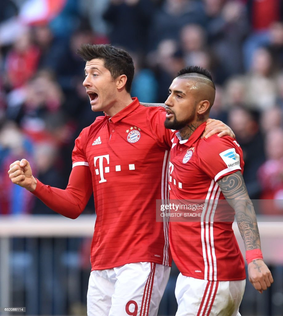 Bayern Munich's Polish striker Robert Lewandowski (L) and Bayern Munich's Chilean midfielder Arturo Vidal (R) react after the first goal for Munich during the German First division Bundesliga football match Bayern Munich vs Eintracht Frankfurt in Munich, southern Germany, on March 11, 2017. / AFP PHOTO / Christof