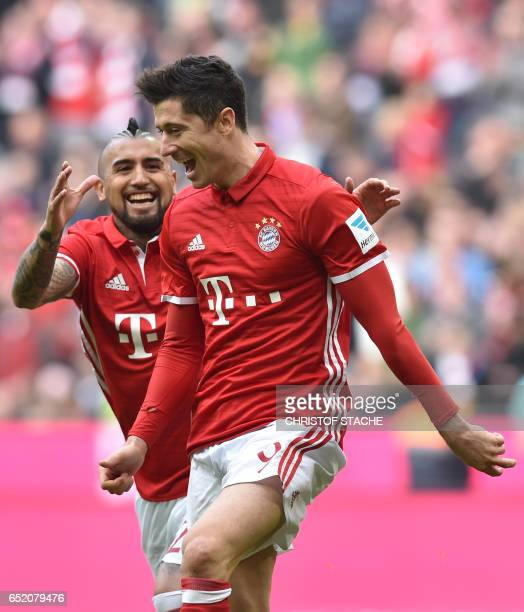 Bayern Munich's Polish striker Robert Lewandowski and Bayern Munich's Chilean midfielder Arturo Vidal celebrate after the third goal for Munich...