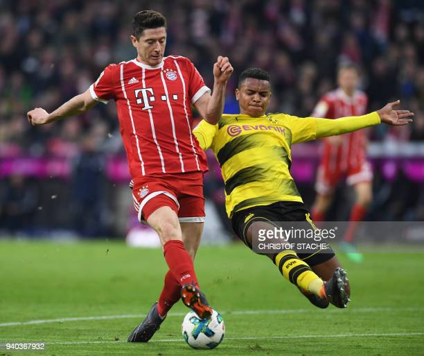 Bayern Munich's Polish striker Robert Lewandowski and Dortmund's Swiss defender Manuel Akanji vie for the ball during the German first division...