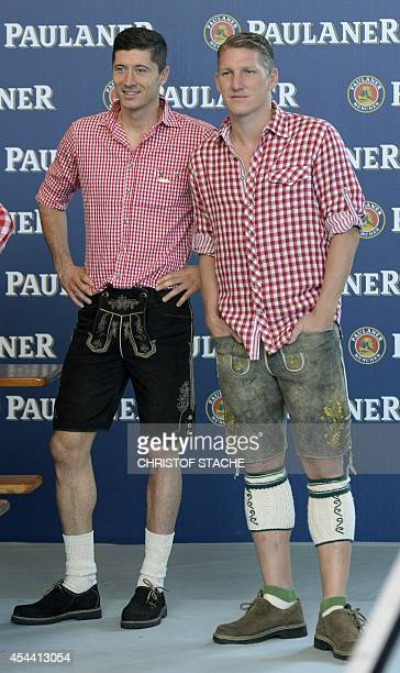 Bayern Munich's Polish striker Robert Lewandowski and his teammate Bayern Munich's midfielder Bastian Schweinsteiger wear leather trousers on the...