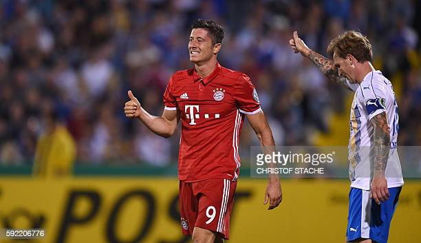 Bayern Munich's Polish striker Robert Lewandowski and Jena's defender Rene Klingbeil react during the German Cup first round football match between...