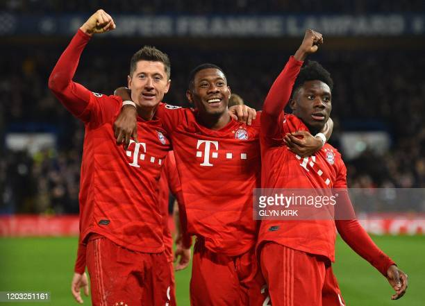 TOPSHOT Bayern Munich's Polish striker Robert Lewandowski celebrates with Bayern Munich's Austrian defender David Alaba and Bayern Munich's Canadian...