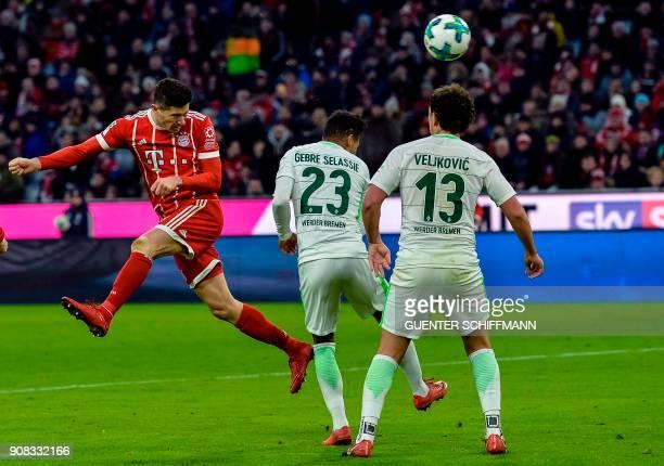 Bayern Munich's Polish striker Robert Lewandowski heads the ball to score a the third goal during the German first division Bundesliga football match...