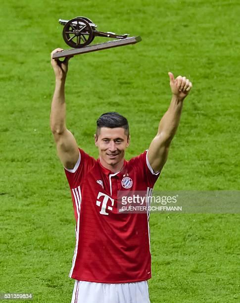 Bayern Munich's Polish striker Robert Lewandowski holds the Bundesliga top scorer trophy aloft after the German first division Bundesliga football...