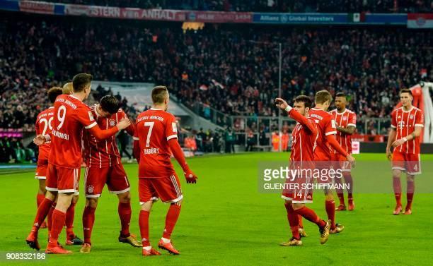 Bayern Munich's Polish striker Robert Lewandowski is congratulated by teammates after scoring a the third goal during the German first division...