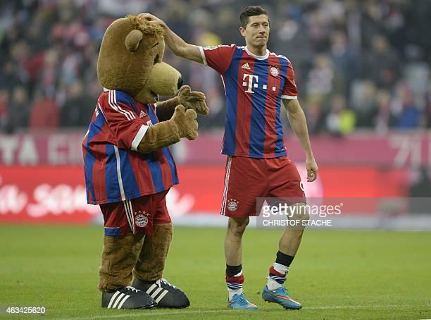Bayern Munich's Polish striker Robert Lewandowski plays with the maskot after the German first division Bundesliga football match FC Bayern Munich vs...
