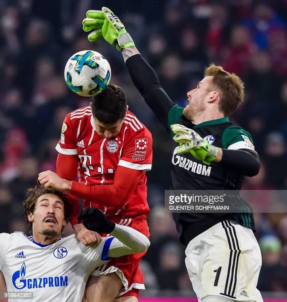 Bayern Munich's Polish striker Robert Lewandowski Schalke's French midfielder Benjamin Stambouli and German goalkeeper Ralf Faehrmann vie for the...