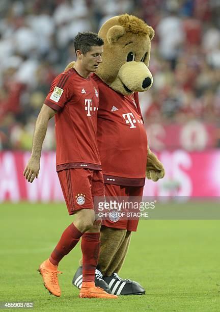 Bayern Munich's Polish striker Robert Lewandowski walks beside the Bayern Munich mascot after the German first division Bundesliga football match...